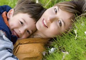 Mother and son laying in grass